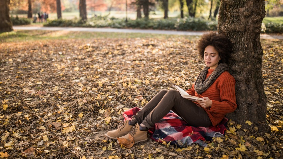 woman reading outdoors in autumn