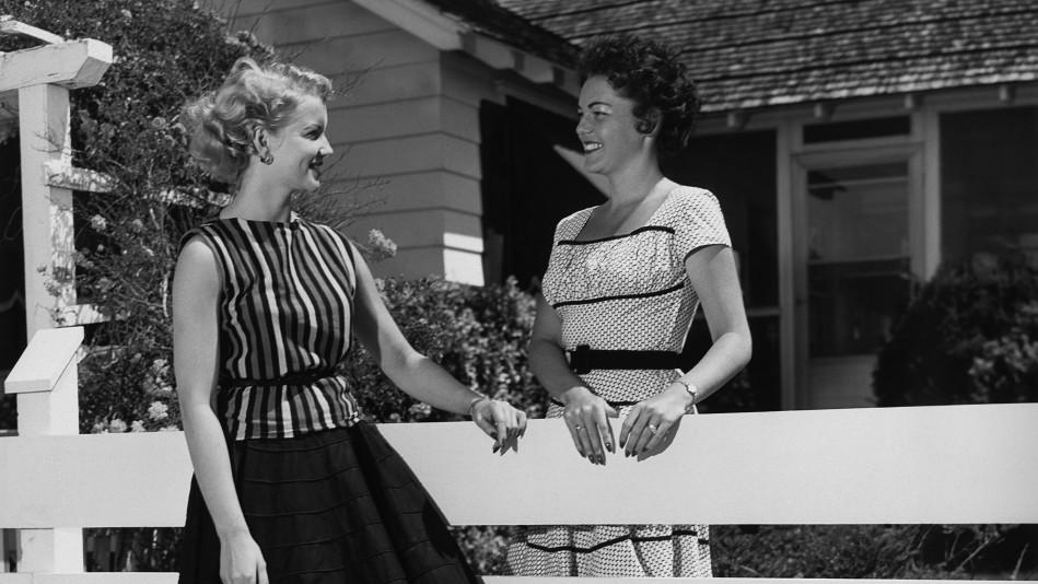 Young women talking near fence
