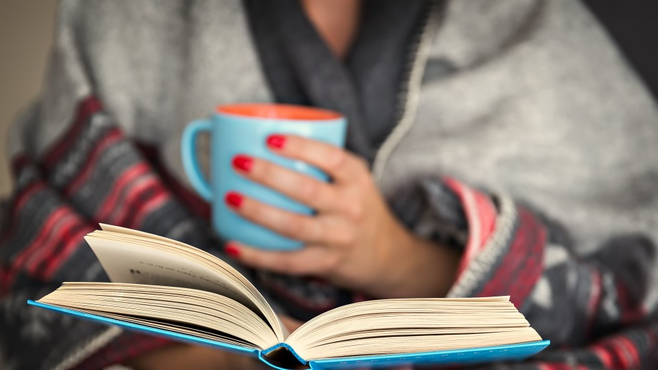 Woman holding a book in one hand and a mug in her other hand