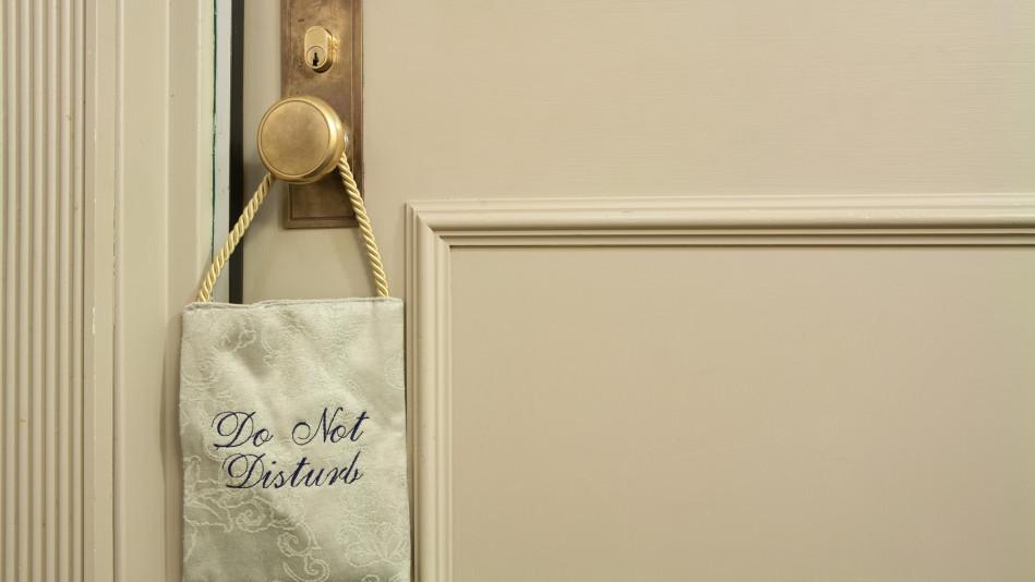 'Do Not Disturb' sign hanging on bedroom door
