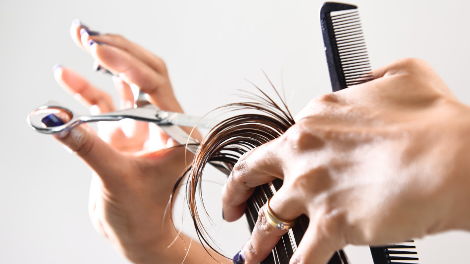 Hairdresser trimming a customer's hair