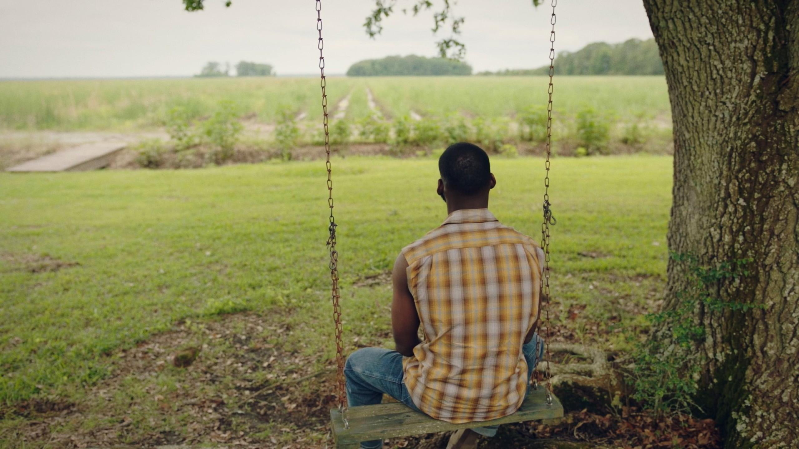 Kofi Siriboe as Ralph Angel Bordelon, sits on a swing.