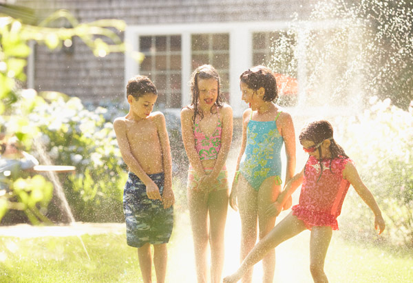 Children run through a sprinkler