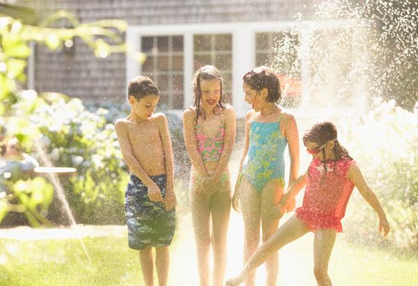 Children run through a sprinkler