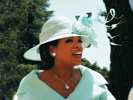 Oprah wearing a hat of feathers and silk roses