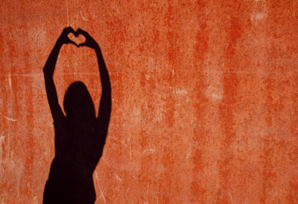 Woman making a shadow heart on the wall
