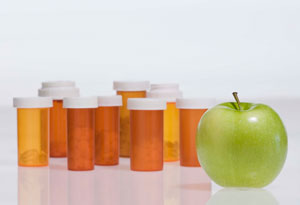 pill bottles with apple in foreground
