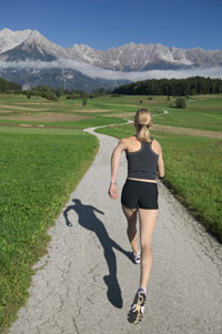 Woman running toward mountains