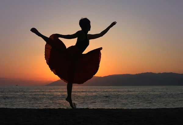 Ballet dancer on the beach at sunset