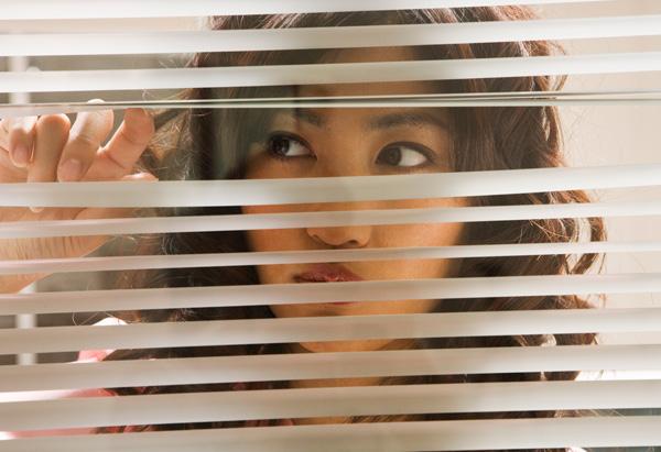 woman peering through window blinds