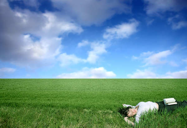 Woman laying in grass with book