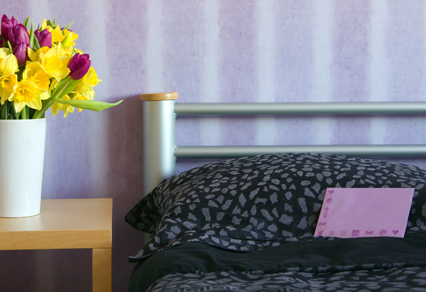 Flowers and a note on a bed