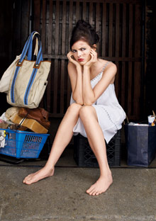 Woman sitting on a milk crate, next to her possessions