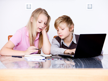 Teenage girl working on computer with younger boy