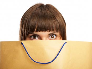 Woman hiding behind a shopping bag