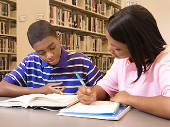 Teenage girl tutoring younger boy