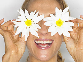 Woman holding daisies up to her eyes
