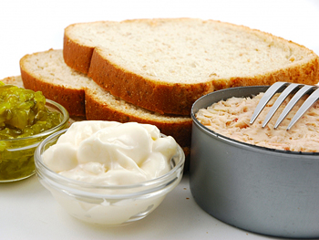 Can of tuna, relish, mayonnaise and white bread