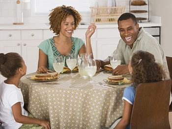 Family eating sandwiches at the dinner table