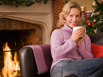 Woman sitting by fireplace and Christmas tree