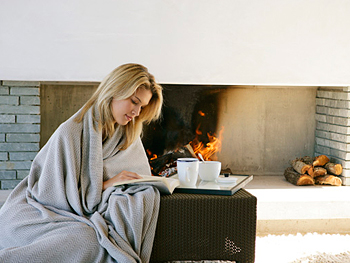 Woman in a blanket reading a book by the fire