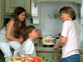 Mother cooking and talking with children