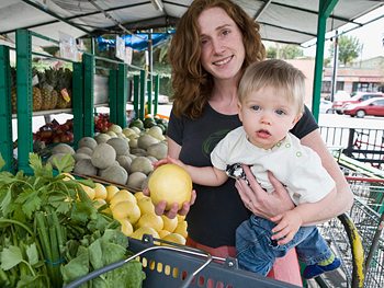 Mother shopping for fruit with her baby