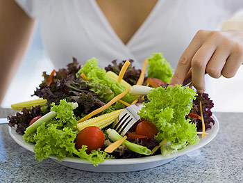 Woman sitting with a large salad
