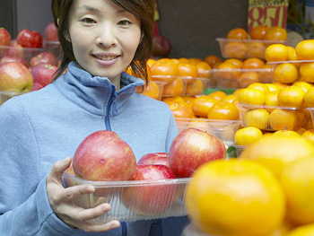 Woman holding container of fruit