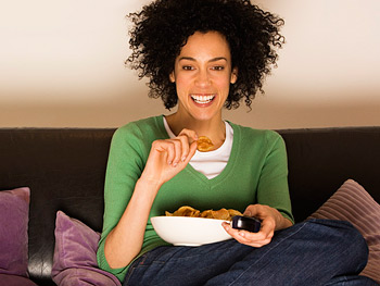 Woman eating on sofa