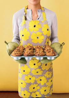 Woman holding baking tin of muffins