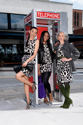 Three women at a phone booth wearing animal prints