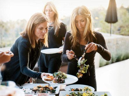 Jennifer Aniston serving salad to Kristin Hahn
