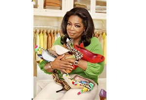 Oprah in her closet holding shoes