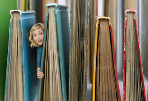 Woman peeking out from behind books