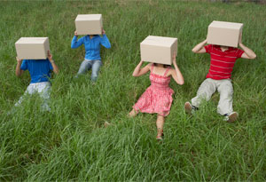 Four people with boxes on their heads sitting in the grass