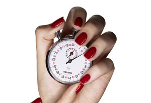 manicured hand holding a stopwatch