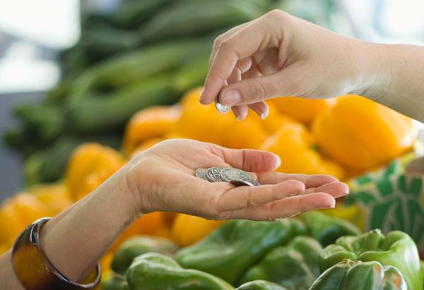 Handing coin over veggies