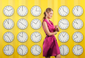 Woman checking her watch, surrounded by clocks
