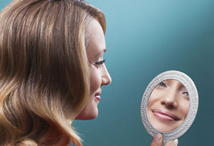 woman looking in hand mirror