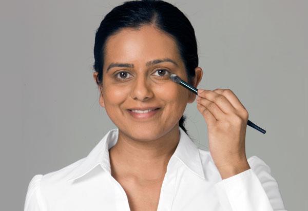 Naik applying concealer with brush