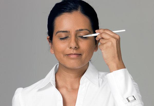 Naik applying black eyeliner