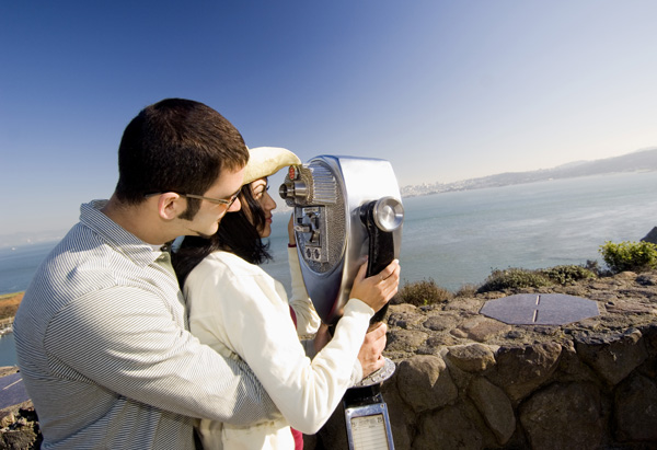 Man and woman looking through telescope