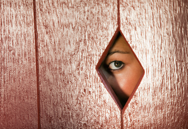 Woman looking through hole in fence