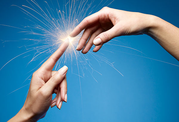 Two hands touching and making sparks