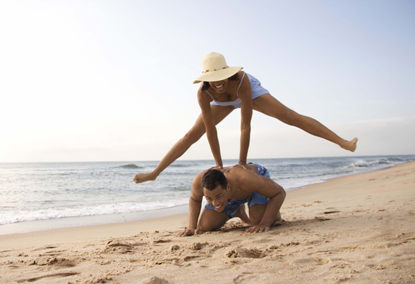 Couple plays leapfrog in the sand