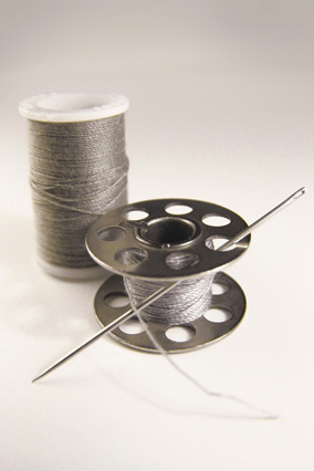 Silver thread, spool and needle