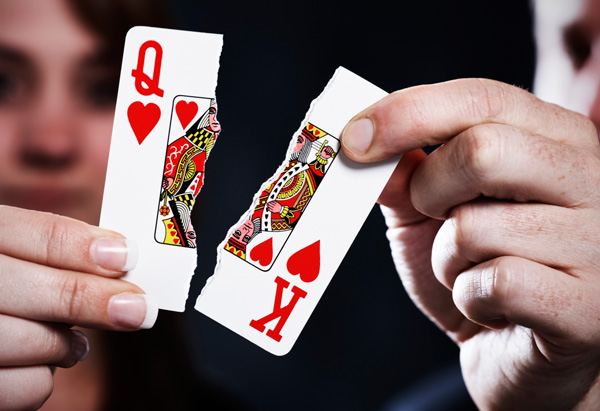 Hands holding torn queen and king playing cards