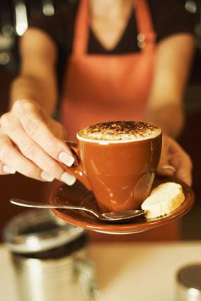 Barista holding cappuccino