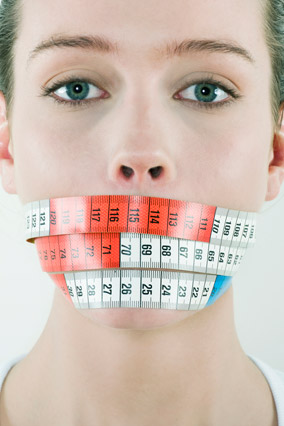 Woman with measuring tape around her mouth